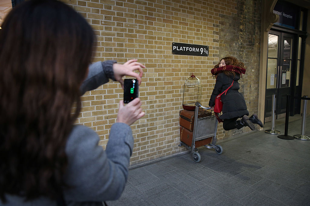 A true tourist re-enacts a scene from Harry Potter at Kings Cross station on January 2, 2013 in London, England. Rail fares have today risen by an average of 4.2% in England, Scotland and Wales, the tenth year in a row that fares have increased above inflation.
