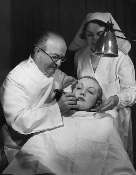 1937: Plastic surgeon J C Bell at work on a customer's face in his beauty parlour. (Photo by Fox Photos/Getty Images)