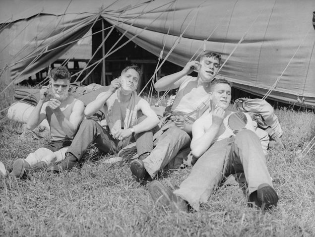 June 1935: Members of the 26th Armoured Car Company of the Territorial Army shaving during a camp in Cayton Bay.