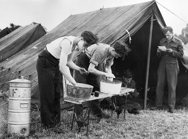 8th July 1944: RAF ground staff wash and shave at tin basins after a day's work refitting Spitfire aircraft at their squadron's camp.