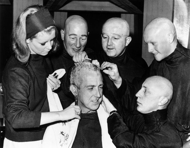 22nd October 1965: Hair stylist Joan Barrett shaves the head of actor David Freed, the last of the actors to be prepared for playing 'Teknix' in a Dr Who television special.