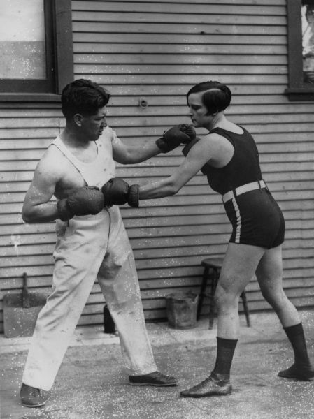 April 1926: American boxer Joe Rivers sparring with Louise Adler, the women's lightweight champion of the world, during a training session before she defends her title.