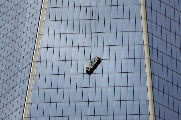 NEW YORK, NY - NOVEMBER 12: A scaffold carrying two workers hangs 69 floors up at 1 World Trade Center on November 12, 2014 in New York City. The workers were washing windows 69 floors up soon after 1 World Trade Center, the tallest building in the Western Hemisphere, opened.