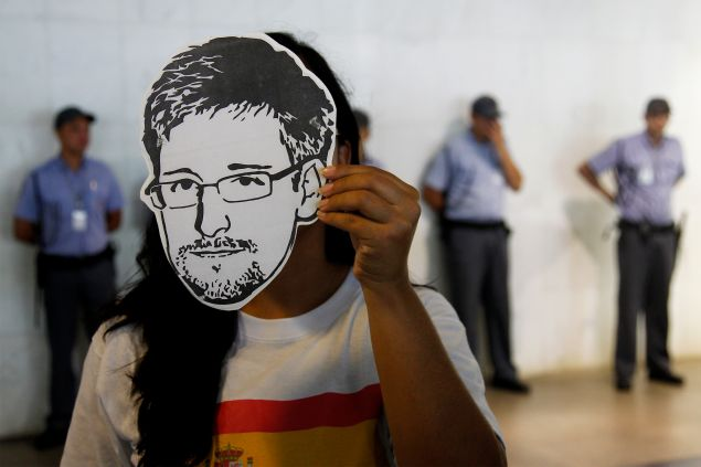 """A member of the Avaaz online community organization wears a """"Snowden"""" mask during the delivery at the the Itamaraty Foreign Ministry Palace of signatures supporting the granting of political asylum by Brazilian President Dilma Rousseff to Edward Snowden, in Brasilia, on February 13, 2014"""