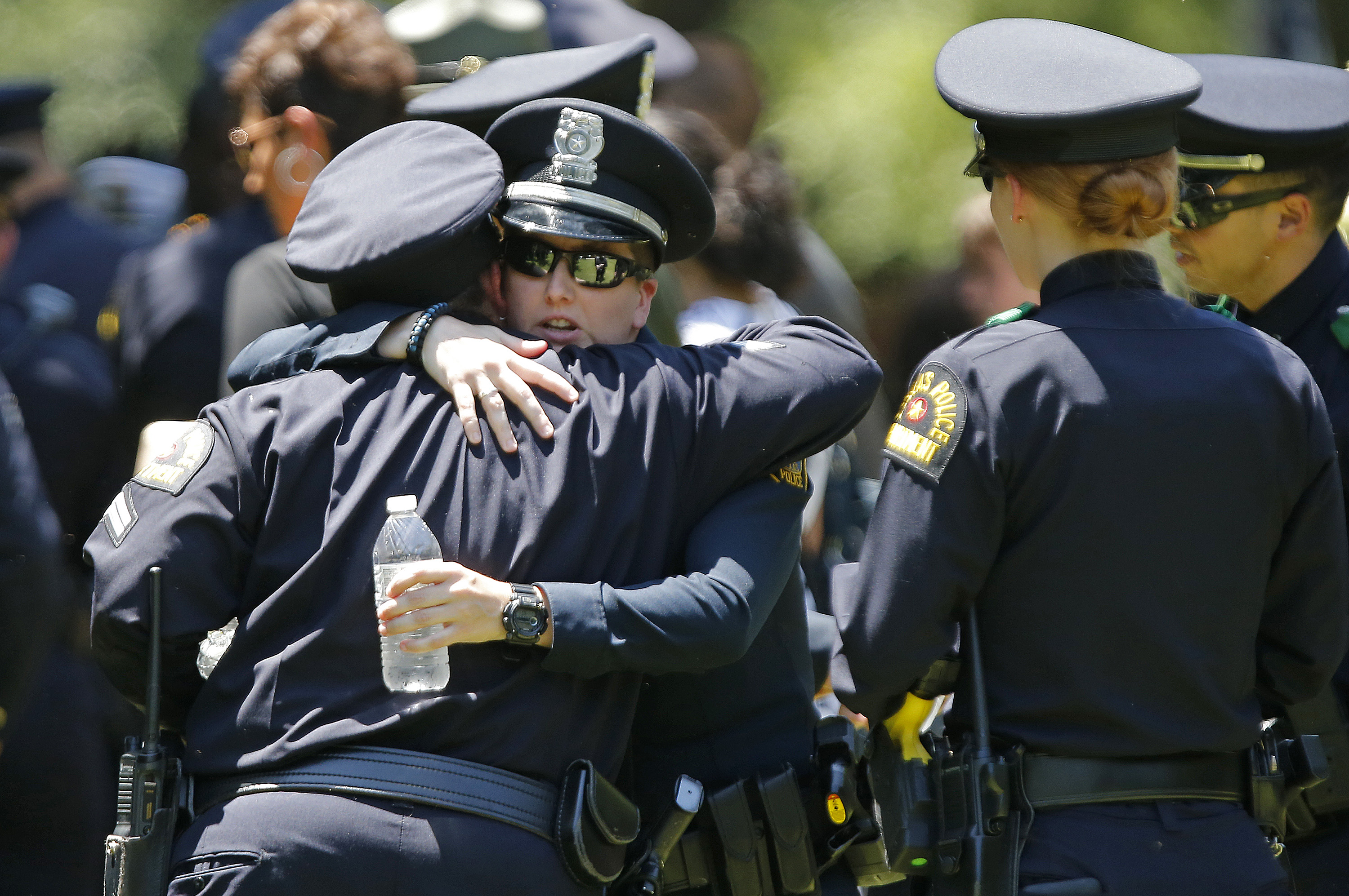 Dallas police officers comfort one another at the graveside service for Senior Corporal Lorne Ahrens on July 13, 2016