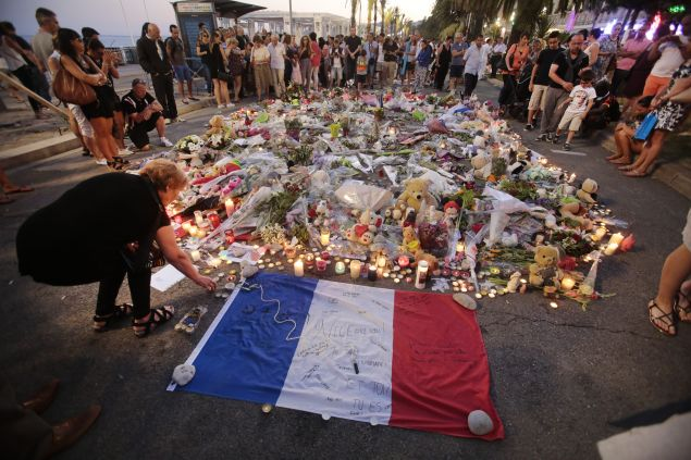 People gather and lay tributes on the Promenade des Anglais on July 17, 2016 in Nice, France.A French-Tunisian attacker killed 84 people as he drove a lorry through crowds, gathered to watch a firework display during Bastille Day Celebrations. The attacker then opened fire on people in the crowd before being shot dead by police.