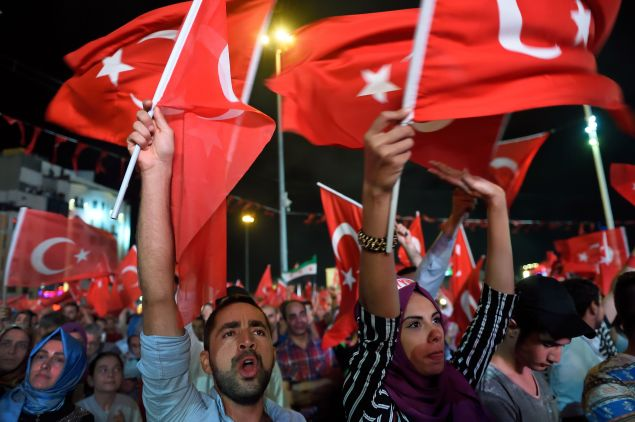 Pro Erdogan supporters hold Turkish national flags during a rally at Taksim square at Istanbul on July 20, 2016 following the failed military coup attempt of July 15.