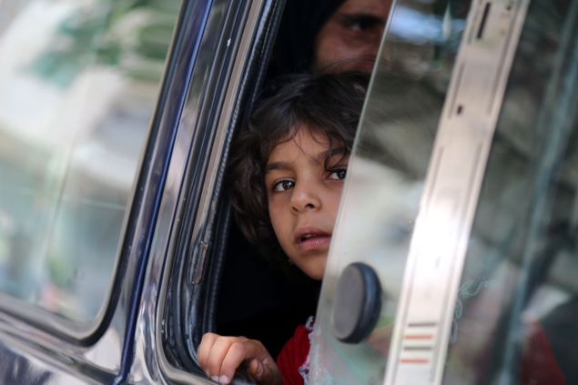 """A Syrian child in a vehicle looks on in the northern Syrian town of Manbij as civilians go back to their homes on August 14, 2016 more than a week after the Arab-Kurdish alliance, known as the Syrian Democratic Forces (SDF), pushed the Islamic State (IS) group out of the city. The last remaining IS fighters abandoned the city of Manbij near the Turkish border on August 12, 2016 after a rout the Pentagon said showed the extremists were """"on the ropes"""". The retreat from the city which IS captured in 2014 was the jihadists' worst defeat yet at the hands of the SDF backed by US air power."""