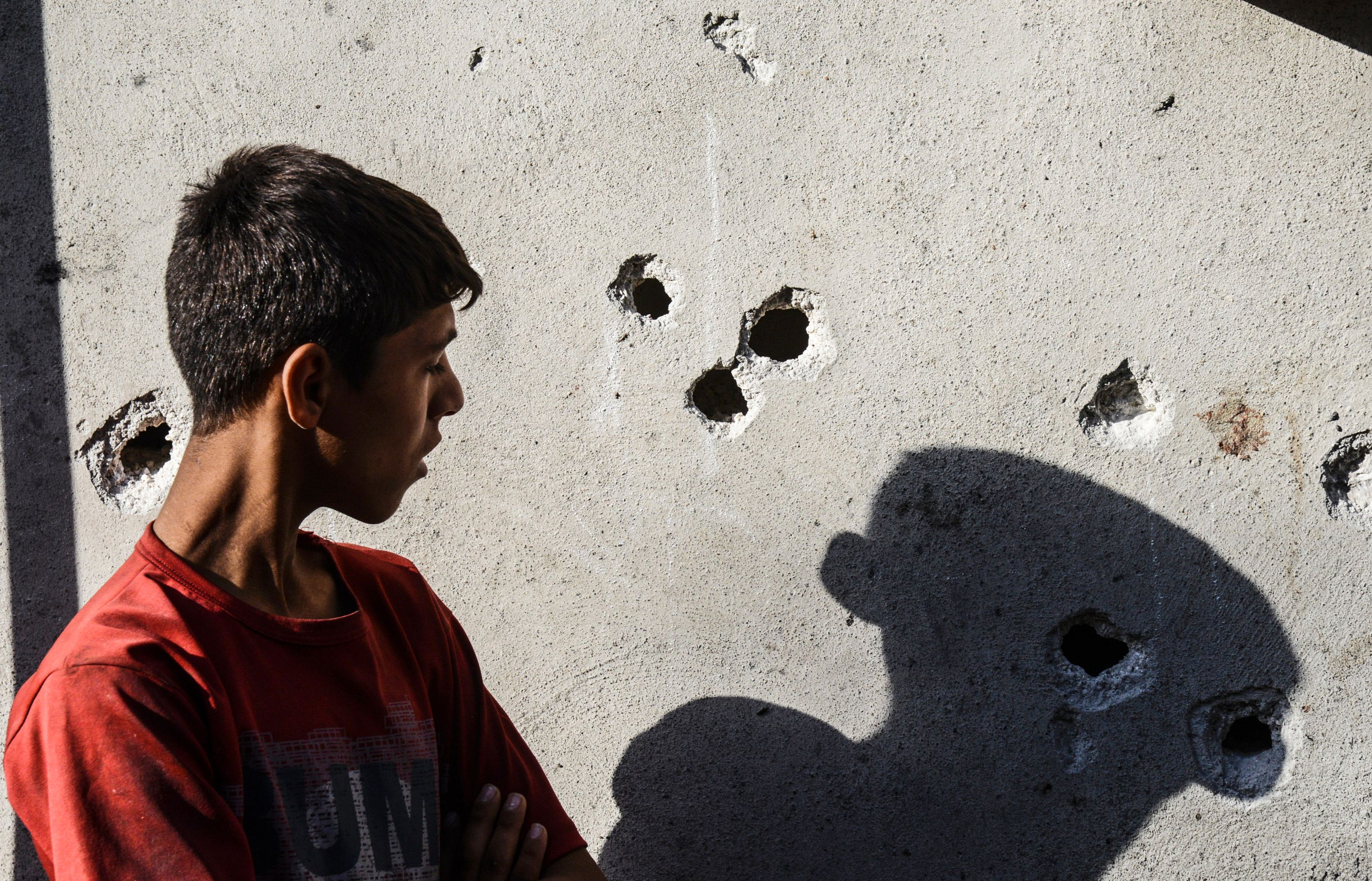 """A boy stands near impacts of projectile on a wall near the explosion scene in Gaziantep in southeastern Turkey near the Syrian border on August 21, 2016. Turkish President Recep Tayyip Erdogan on Sunday said the Islamic State (IS) group was the """"likely perpetrator"""" of the bomb attack."""