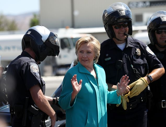 RENO, NV - AUGUST 25: Democratic presidential nominee former Secretary of State Hillary Clinton talks with Reno police officers before getting onto her plane at Reno Tahoe International Airport on August 25, 2016 in Reno, Nevada. Hillary Clinton delivered a speech about republican presidential nominee Donald Trump's policies