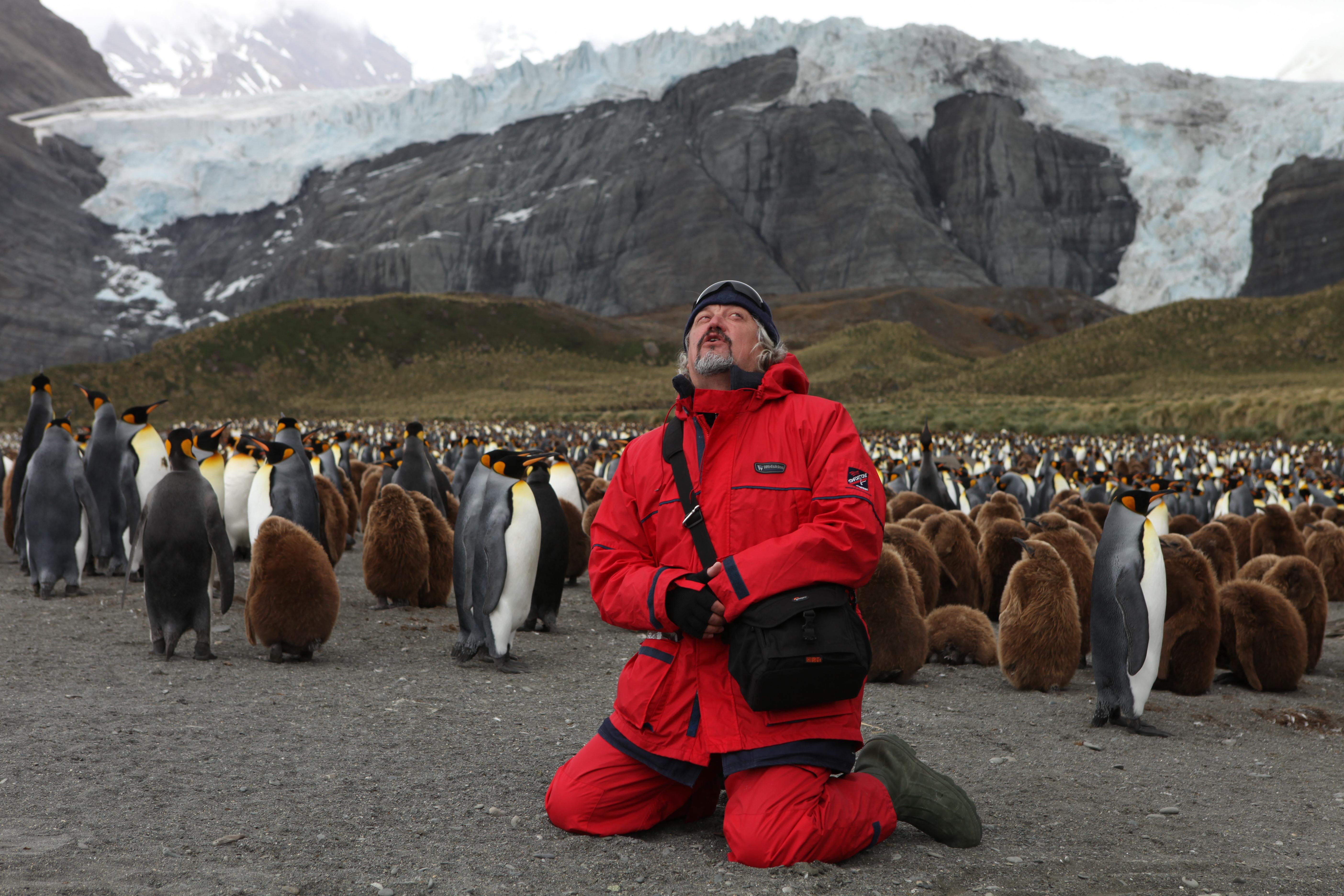 Ponomarev with penguins in Antarctica.