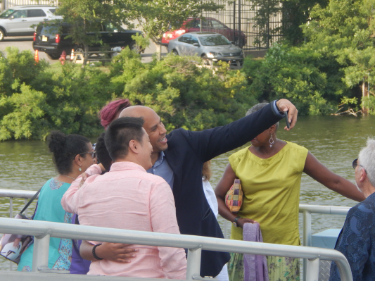 Senator Cory Booker snaps a picture with supporters on his way onto the Battleship New Jersey in Camden's harbor