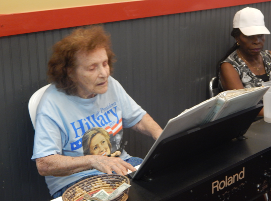 An elderly Clinton supporter plays a halting tune on an electric keyboard inside the market
