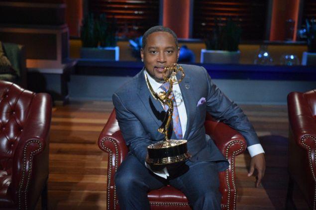 Daymond John holding Shark Tank's most recent Emmy.