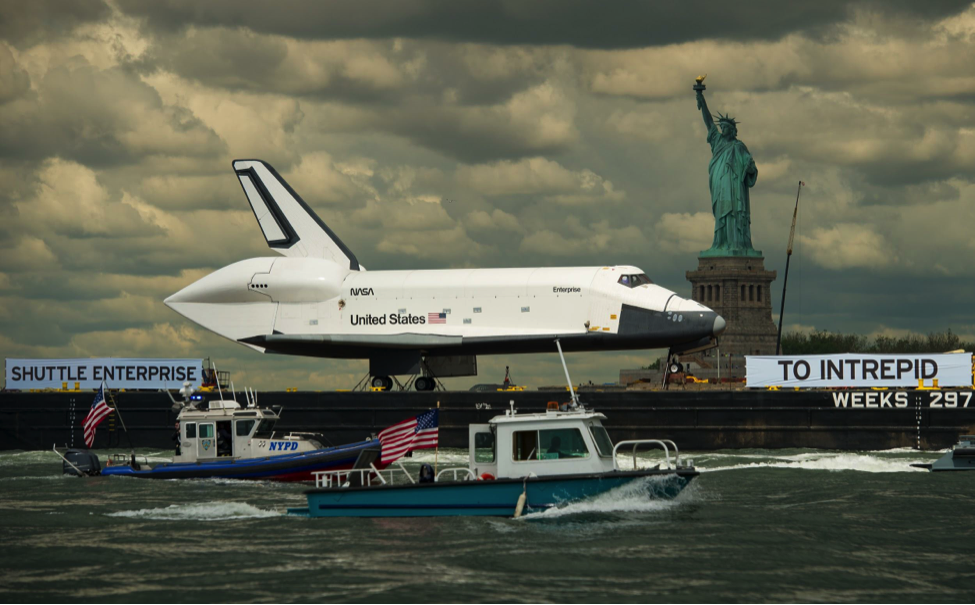 The space shuttle Enterprise being towed on the Hudson River past the Statue of Liberty on its way to the Intrepid Sea, Air and Space Museum, its permanent home.