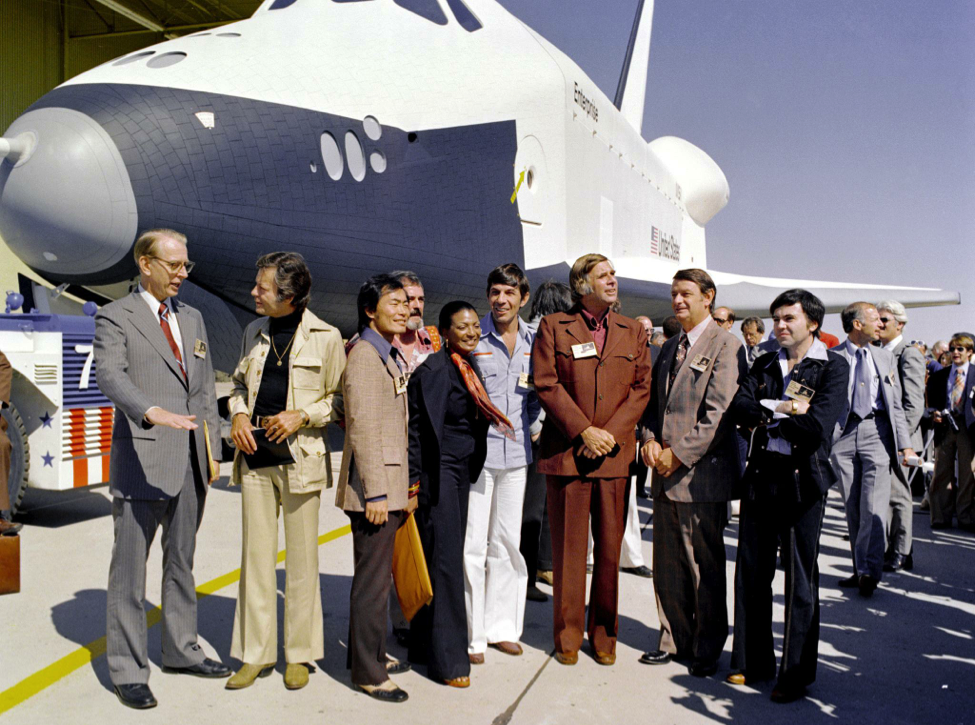 NASA Administrator Fletcher, Gene Roddenberry, and the cast of Star Trek minus William Shatner in front of the newly unveiled space shuttle Enterprise.