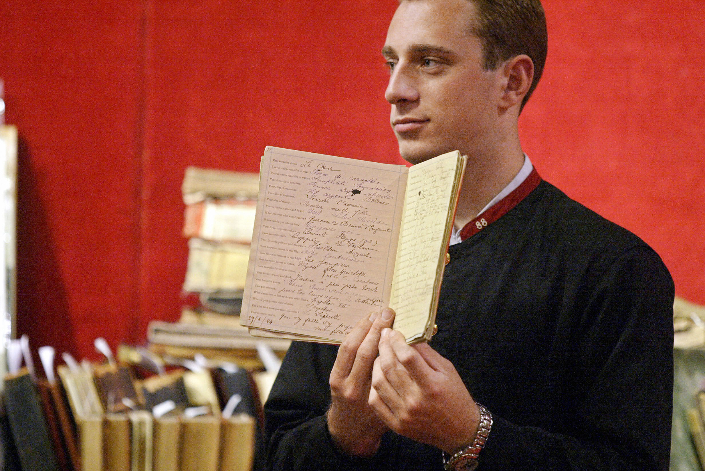 A porter holds up the manuscript of Marcel Proust's questionaire, 27 May 2003 put up for sale in Paris by Beaussant-Lefevre auction house at Drouot hotel in Paris. The manuscript from 1884-1887, conceived by Proust at 14, was sold 120.227 Euro, four time its estimate price, to French designer Gerard Darel.