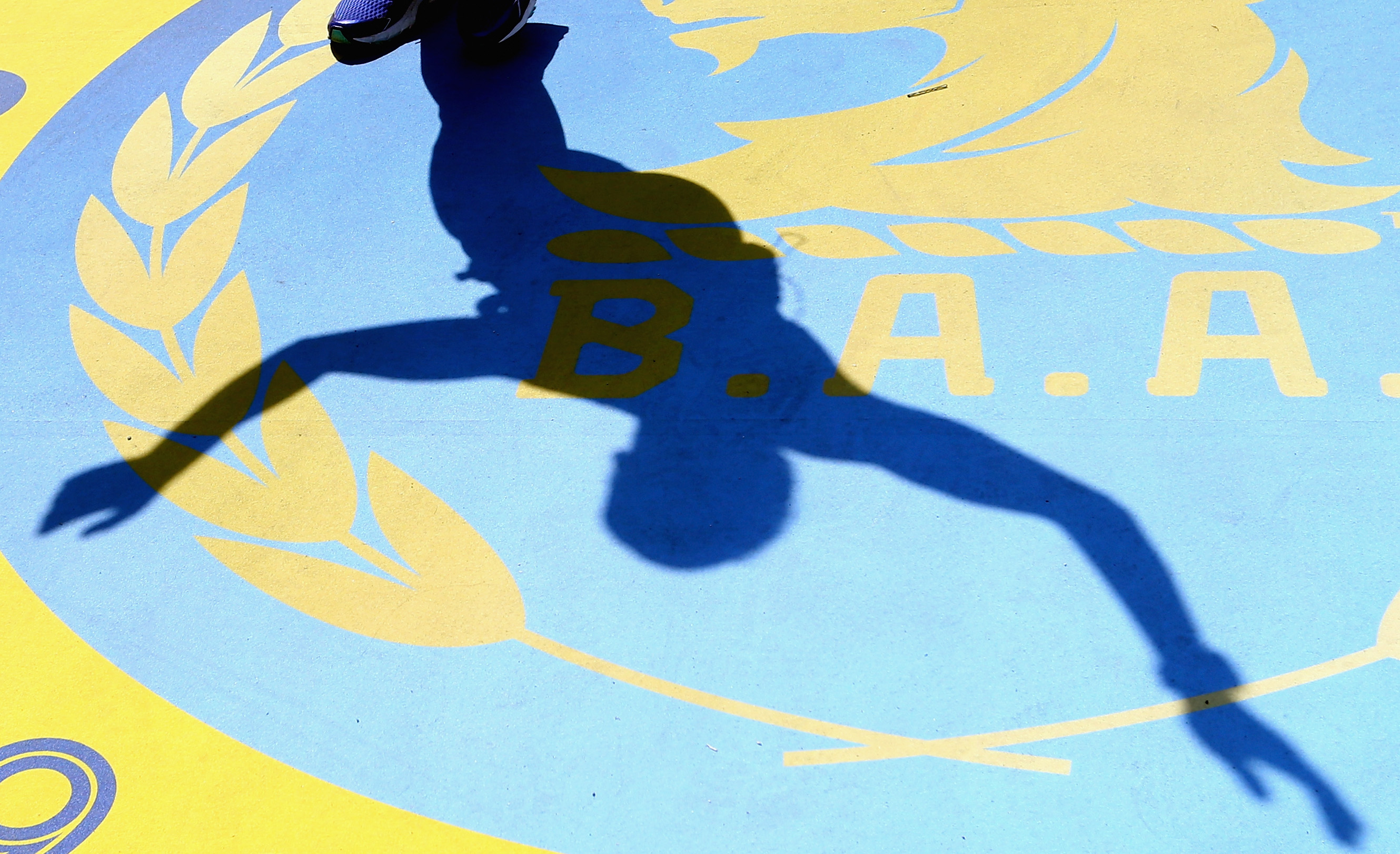 A runner's shadow is seen crossing the finish line during the 120th Boston Marathon.