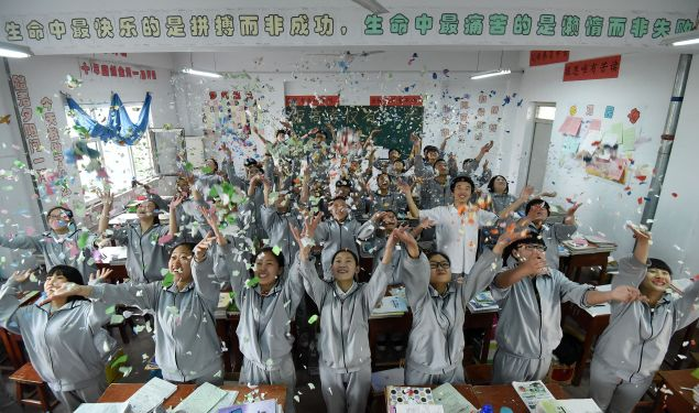 Senior high students cast shredded paper to release stress before the college entrance exams at a high school in Handan, north China's Hebei province