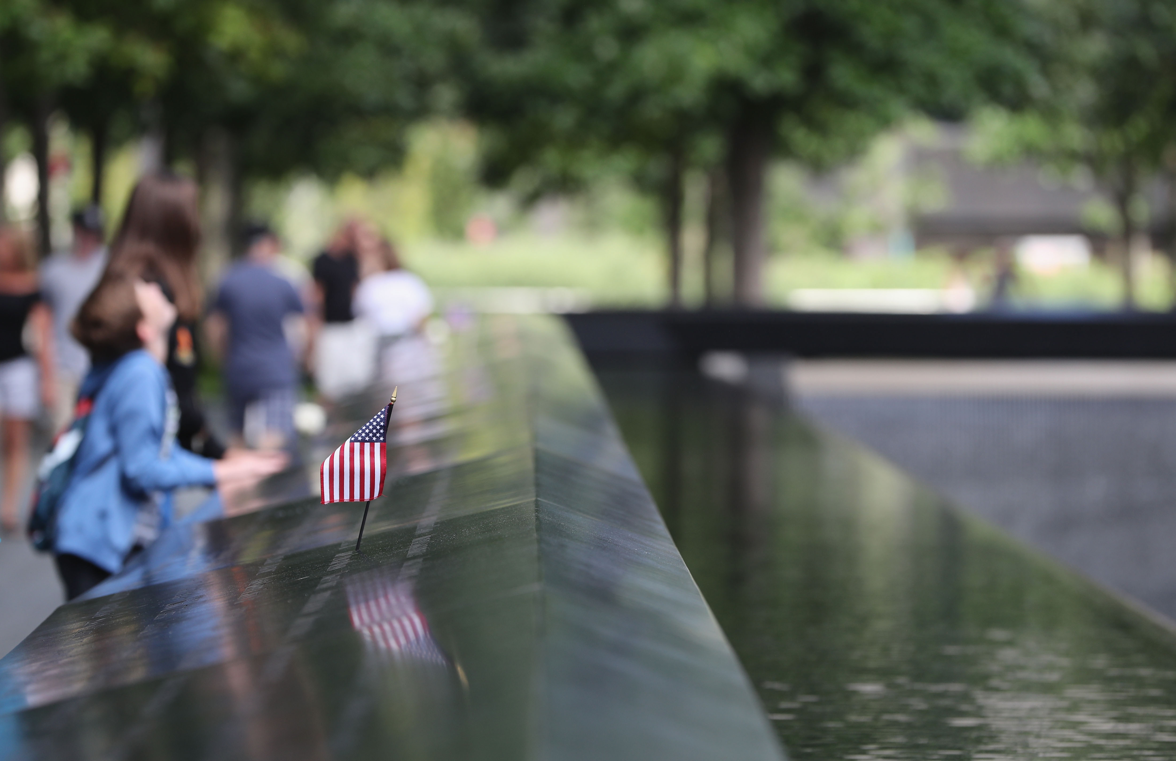 A young boy looks up to One World Trade Center next to a US flag at the the 9/11 memorial site.