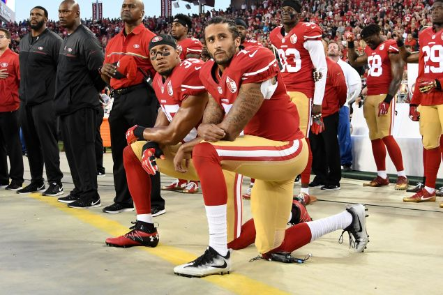 Colin Kaepernick #7 and Eric Reid #35 of the San Francisco 49ers kneel in protest during the national anthem prior to playing the Los Angeles Rams in their NFL game at Levi's Stadium on September 12, 2016.