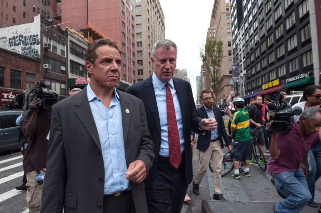"""New York City Mayor Bill de Blasio (R) and New York Gov. Andrew Cuomo tour the site of the bomb blast on 23rd St. in Manhattan's Chelsea neighborhood on September 18, 2016 in New York City.  An explosion that injured 29 people which went off in a construction dumpster is being labeled an """"intentional act"""". A second device, a pressure cooker, was found four blocks away that an early investigation found was likely also a bomb."""