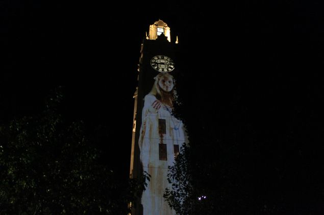 """""""Suzanne"""" projected on the clock tower at Montreal's old port."""