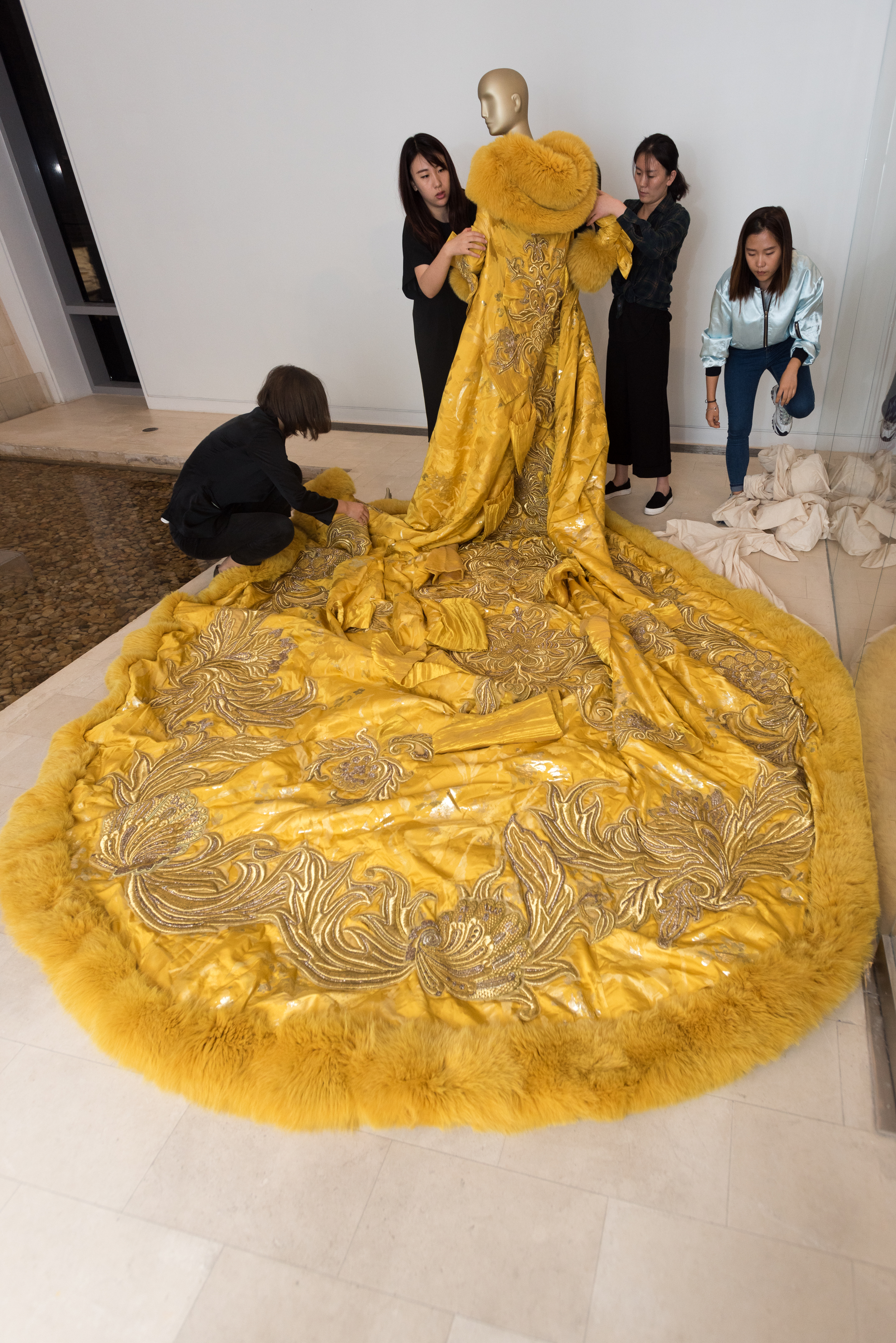 Volunteers at the China Institute dress a mannequin with the dress worn by Rihanna to the Met Gala.