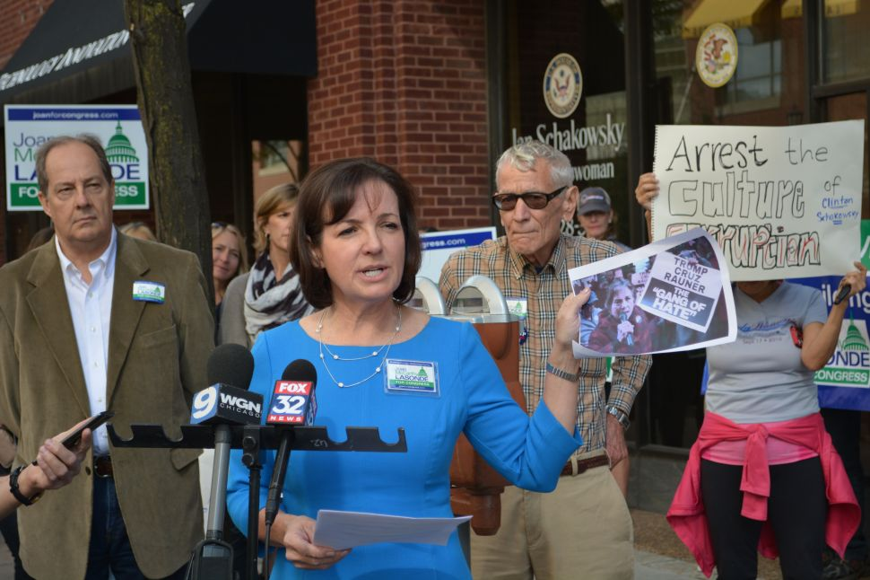 "This is Joan McCarthy Lasonde at her press conference in front of Jan's district office in downtown Evanston. Lasonde demanded that Schakowsky resign based on her alleged complicity in what Lasonde referred to as ""orchestrated political violence."" The photo she's holding up is Jan at a rally outside the Governor's Dinner in downtown Chicago holding up the ""Gang of Hate"" sign printed by her husband's subcontractors at Americans United for Change."