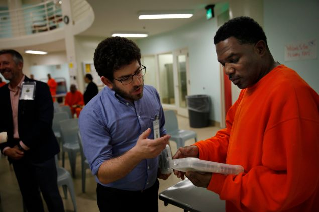 APDS instructor Dylan Alban introduces an APDS tablet to an inmate in the San Francisco County Jail.