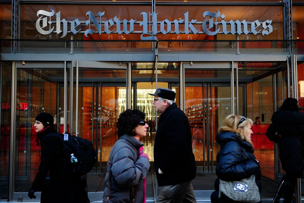 People walk by the entrance to US newspaper 'The New York Times' in New York, March 8, 2011