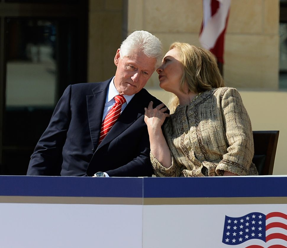 Former first lady and former Secretary of State Hillary Rodham Clinton speaks with her husband former president Bill Clinton as they attend the opening ceremony of the George W. Bush Presidential Center April 25, 2013 in Dallas, Texas
