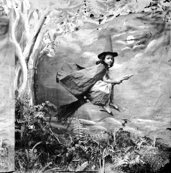 A young girl dressed as a witch suspended mid-air on a broomstick circa 1865.