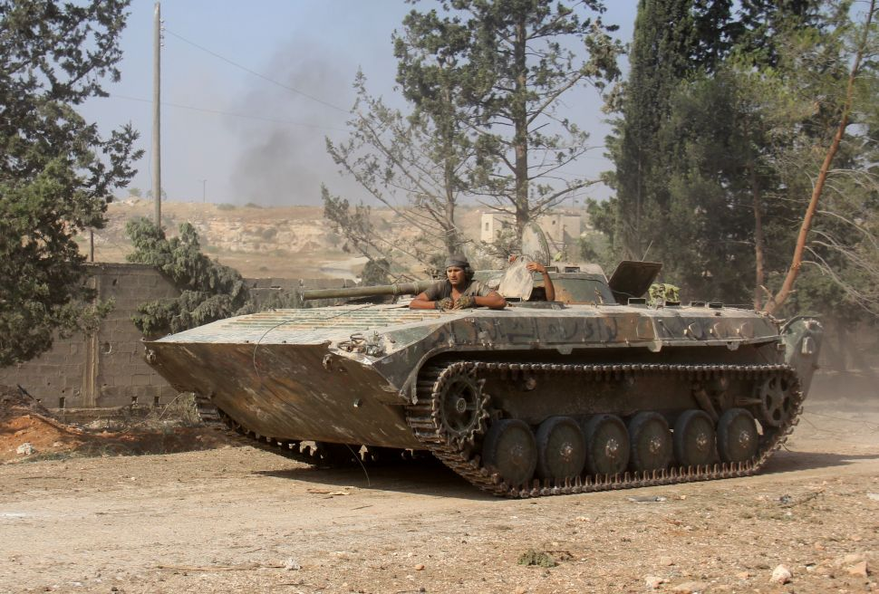Fighters from the former Al-Nusra Front -- renamed Fateh al-Sham Front after breaking from Al-Qaeda -- drive a tank as they seized key positions south of Aleppo on August 6, 2016