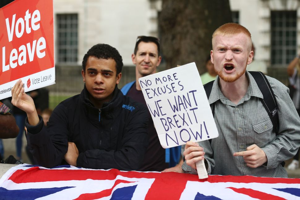 A man carrying an anti-EU pro-Brexit placard shouts in a counter protest against pro-Europe marchers on a March for Europe demonstration against the Brexit vote in Parliament Square in central London on September 3, 2016