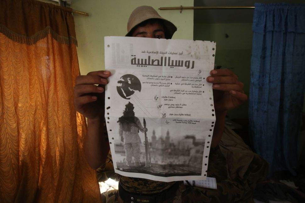 A Sunni fighter from the Popular Mobilisation Units supporting the government forces holds up a document he found in a building in the town of Sharqat around 80 kilometres (50 miles) south of the city of Mosul, giving details on IS's campaign against Russia the day after they recaptured the northern town from the Islamic State (IS) group on September 23, 2016, Security forces began the operation on September 20, 2016 to oust the Islamic State group from Sharqat, a town near supply lines needed for the battle to retake second city Mosul from the jihadists.