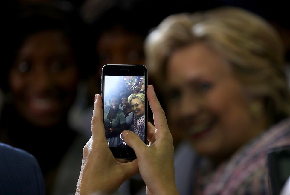 Democratic presidential nominee former Secretary of State Hillary Clinton takes a selfie with a supporter during a campaign rally at Coral Springs Gymnasium on September 30, 2016 in Coral Springs, Florida. Hillary Clinton is campaigning in Florida.