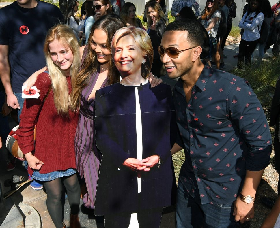 UNLV student Alexandra Olianna (L) poses with model and television personality Chrissy Teigen (2nd L), singer/songwriter John Legend (R) and a cardboard cutout of Democratic presidential nominee Hillary Clinton during a voter registration drive at UNLV on October 4, 2016 in Las Vegas