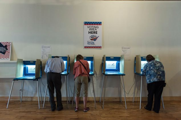 Three people vote in booths at the Early Vote Center in northeast Minneapolis, Minnesota on October 5, 2016.