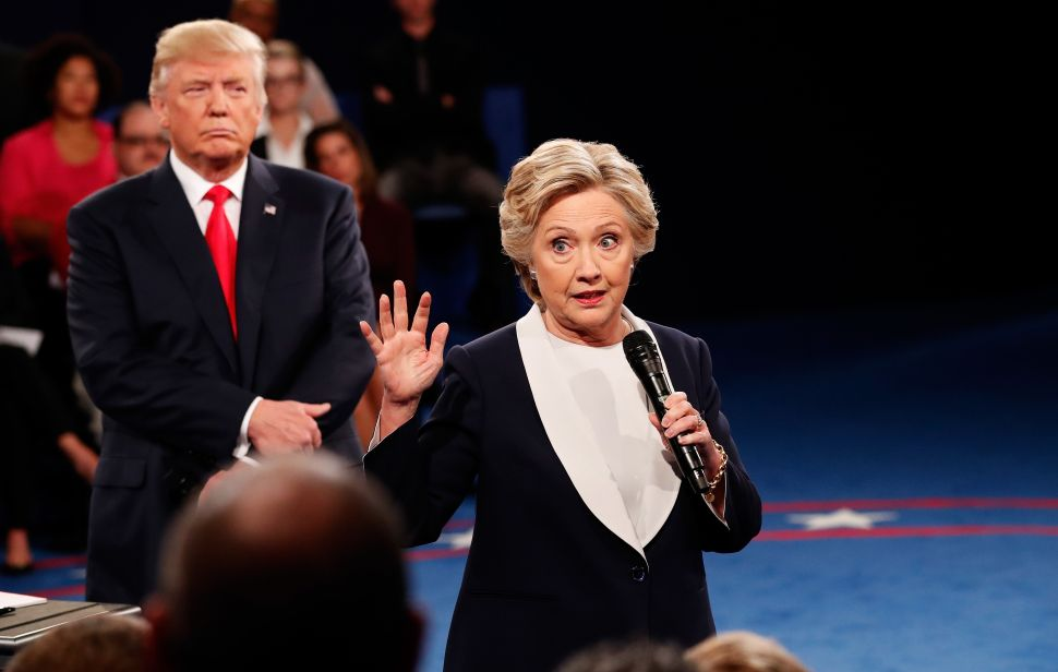 ST LOUIS, MO - OCTOBER 09: Democratic presidential nominee former Secretary of State Hillary Clinton (R) speaks as Republican presidential nominee Donald Trump listens during the town hall debate at Washington University on October 9, 2016 in St Louis, Missouri. This is the second of three presidential debates scheduled prior to the November 8th election.