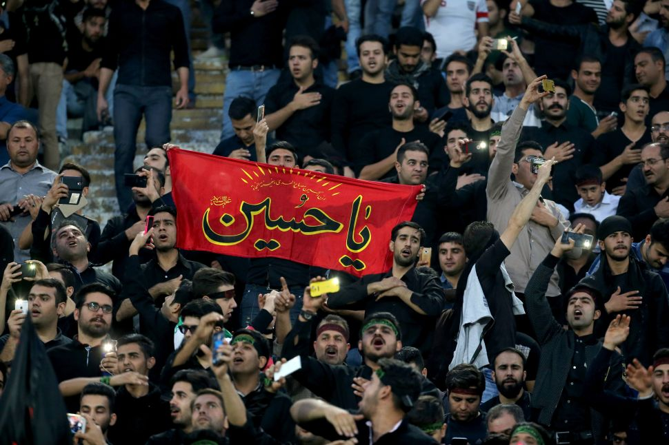 Iranian fans wave a religious banner to mark Ashura, which marks the death of Prophet Mohammed's grandson Imam Hussein in the seventh century, during the 2018 World Cup qualifying football match between Iran and South Korea at the Azadi Stadium in Tehran on October 11, 2016. / AFP / ATTA KENARE