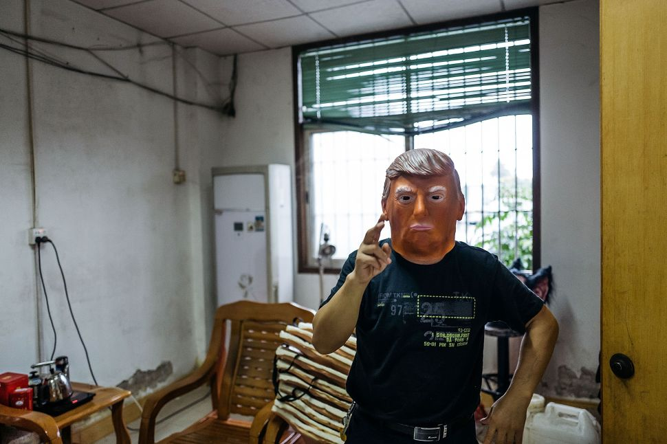 SHENZHEN, CHINA - OCTOBER 18: An employee wearing a mask of Donald Trump poses for a photograph at the Shenzhen Lanbingcai Latex Crafts Factory on October 18, 2016 in Shenzhen, China. Shenzhen Lanbingcai Latex Crafts Factory, located in the industrial area of Shenzhen with 20 to 30 employees, produces all sort of Halloween and party costumes and masks. It runs a small scale production of Donald Trump masks for local distribution within mainland China costing from 30 Renminbi onwards as the third Presidential Debate 2016 between Donald Trump and Hillary Clinton happens on Thursday. Chinese media have derided the election as a risible variety show in which the candidates' spectacular personal failings have taken precedence over the business of governance.
