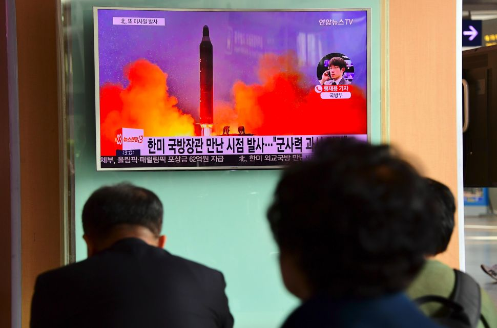 People watch a television news report showing file footage of North Korea's missile launch at a railway station in Seoul.