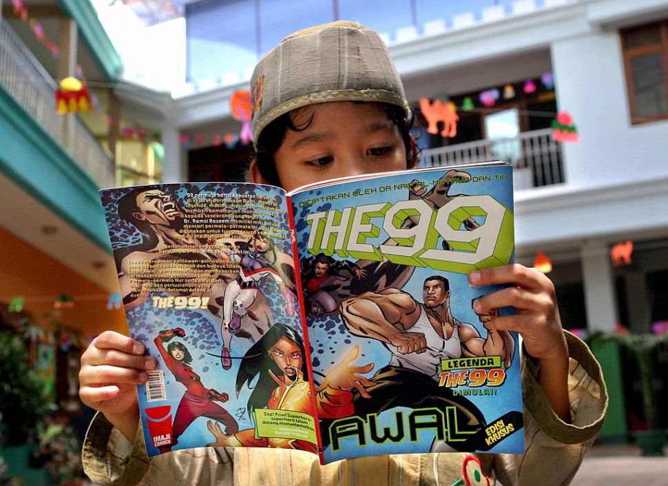 "COMIC by Nabiha Shahab A young boy reads a copy of the ""The 99"" comic book at his school in Jakarta, 01 October 2007. Jabbar the Powerful, the alter-ego of teenager Nawaf Al-Bilali, is the first of 99 superhero characters in an Islamic culture-based comic book series, ""The 99"", launched this month in Indonesia. The comic seeks to act as a metaphor for what's happening in the Islamic world, its creator, Kuwaiti-born Naif Al-Mutawa, told Agence France Presse (AFP). AFP PHOTO/ADEK BERRY"