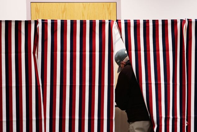 A man marks his ballot in a voting booth in Manchester, New Hampshire.