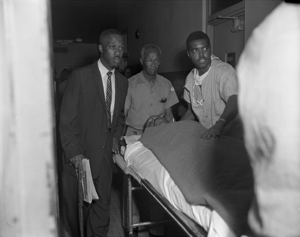 With the letter opener still protruding from his chest, Dr. Martin Luther King is wheeled into Harlem Hospital for treatment after being stabbed.