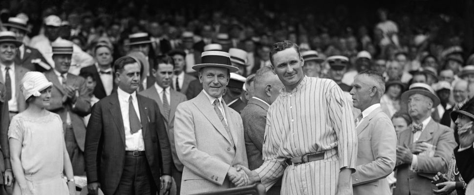 President Calvin Coolidge shakes hands with pitcher Walter Johnson.