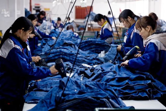 "XINTANG, CHINA - Workers manufacture blue jeans in Congshin textile factory on February 9, 2012 in Xintang, Guangdong province, China.The town of Xintang, nicknamed ""the denim jeans center of the world, claims to produce 60% of the world global output of jeans."
