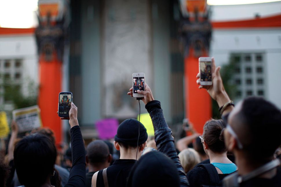 LOS ANGELES, CA - DECEMBER 6: People aim cell phones at a speaker in front of the TCL Chinese Theatre as they march on Hollywood Boulevard to protest of the decision in New York not to indict a police officer involved in the choke-hold death of Eric Garner on December 6, 2014 in the Hollywood section of Los Angeles, California. The march passed the tourist attraction of Hollywood and Highland where police had previously shot and killed a man that according to police had a knife. (Photo by David McNew/Getty Images)
