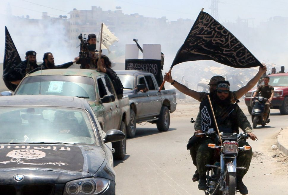Fighters from Al-Qaeda's Syrian affiliate Al-Nusra Front drive in the northern Syrian city of Aleppo flying Islamist flags as they head to a frontline, on May 26, 2015. Once Syria's economic powerhouse, Aleppo has been divided between government control in the city's west and rebel control in the east since shortly after fighting there began in mid-2012. AFP PHOTO / AMC / FADI AL-HALABI